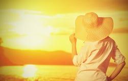 Är beundrar den lyckliga kvinnan för skönhet i hennes hatt tillbaka och solnedgång över havet Royaltyfri Foto
