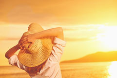Är beundrar den lyckliga kvinnan för skönhet i hennes hatt tillbaka och solnedgång över havet Royaltyfri Bild