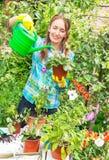 Är den aktiva lyckliga flickan för trädgårdsmästaren rymma och bevattna krukan av blomman Arkivfoto