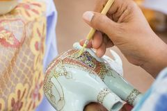 Är den arbetande showen för specialistfolk processen av att måla keramisk benjarong traditionellt thailändskt Royaltyfri Foto