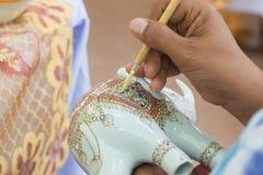 Är den arbetande showen för specialistfolk processen av att måla keramisk benjarong traditionellt thailändskt Arkivbild