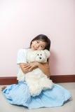 Är den asiatiska thai nationaliteten för barnlilla flickan med den vita leksaknallen Arkivbild