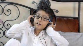 Är den caucasian pojken för den gulliga lilla indiska asiatet med lyssnande musik för anblickar på headphonedans som nickar huvud