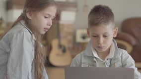 Är den förtjusande koncentrera pojken för ståenden skriva eller spela på bärbara datorn och hans tvilling- syster som håller ögon lager videofilmer