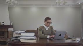 Är den förtjusande unga mannen för ståenden i exponeringsglas som sitter på trätabellen i kontoret, många böcker, på tabellen Ner arkivfilmer