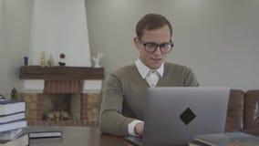 Är den förtjusande unga mannen för ståenden i exponeringsglas som sitter på trätabellen i kontoret, många böcker, på tabellen arkivfilmer