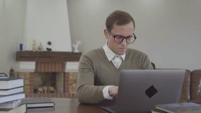 Är den förtjusande unga mannen för ståenden i exponeringsglas som sitter på trätabellen i kontoret, många böcker, på tabellen gul stock video