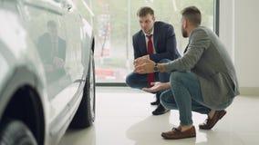 Är den gladlynta kunden för två män och vänskapsmatchrepresentanten tala och göra en gest diskutera bilmodellen, medan squatting  lager videofilmer