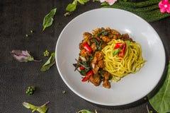 Är den gula nudeln stekte grisköttskalet, chiliavsmakningmeny värt ett försök thai matstil Arkivfoton