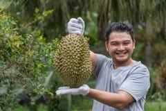 Är den hållande durianen för den asiatiska bonden en konung av frukt arkivbilder