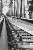 Är den järnväg stången för närbilden och en pojke och en hund som bort går på järnvägsbron, inskriften i ryss, STOPPET! INGET TIL royaltyfria foton