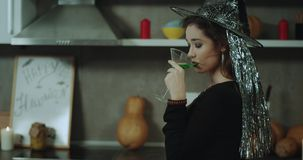 Är den lockiga unga damen för closeupen som maskeras i en häxa, klar för ett allhelgonaaftonparti och att dricka en grön coctail, stock video