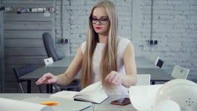 Är den märkes- arbetaren för kontoret sitta och förbereda sig att arbeta på nerarkitektprojektet för tillverkning av det moderna  stock video