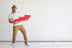Är den stilfulla mannen för den lyckliga skärpan stå och rymma stor röd arro Royaltyfri Fotografi
