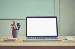 Är den tomma skärmen för bärbara datorn på skrivbordet och handstilutrustningen i mötesrummet där ett vitt bräde på baksidan Royaltyfria Bilder