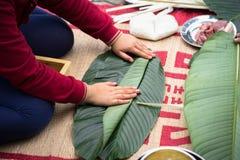 Är den traditionella klänningen Ao Dai som för barnkläder lär att göra Chung att baka ihop vid händer closeupen, den Chung kakan, Arkivbild