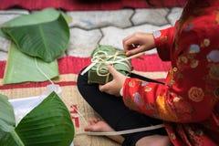 Är den traditionella klänningen Ao Dai som för barnkläder lär att göra Chung att baka ihop vid händer closeupen, den Chung kakan, Arkivfoton