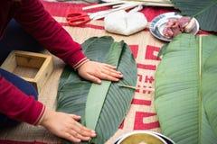 Är den traditionella klänningen Ao Dai som för barnkläder lär att göra Chung att baka ihop vid händer closeupen, den Chung kakan, Arkivbilder