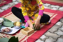 Är den traditionella klänningen Ao Dai som för barnkläder lär att göra Chung att baka ihop vid händer closeupen, den Chung kakan, Fotografering för Bildbyråer