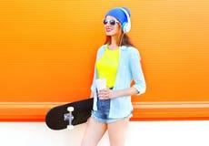 Är den unga kvinnan för mode med skateboarden och kaffe av koppen lyssnar till musik över den färgrika apelsinen Royaltyfri Bild