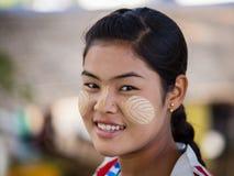 Är den unga Myanmar för ståenden flickan med thanaka på hennes leendeframsida lycka burma Arkivfoto
