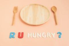 Är du hungrig text med träplattan och bestick Arkivfoto