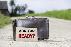 Är du klar? Gammal resande resväska på landsvägen Arkivbilder
