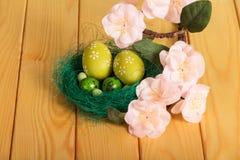 Är förgrena sig olika påskägg i rede och med blommor Royaltyfria Foton