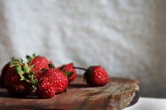Är flera jordgubbar på skärbrädan med vit bakgrund Royaltyfria Foton