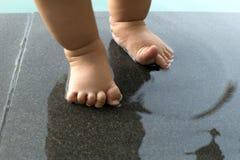 Är foten för behandla som ett barn` ett s våt i pölen Arkivbild