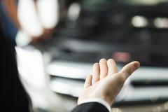 Är här din nya bil. Närbildfors av handen som framlägger en ca Royaltyfria Bilder