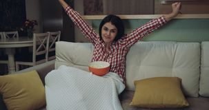 Är hållande ögonen på tv för den unga kvinnan som äter popcornet och, mycket upphetsad lager videofilmer