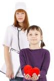 Är hållande flott hjärta för lilla flickan och den pediatriska doktorskvinnan Arkivfoto