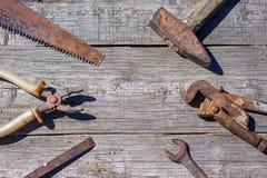 Är hjälpmedlen på träbakgrundshammareplattång och den öppna skiftnyckeln Royaltyfri Fotografi