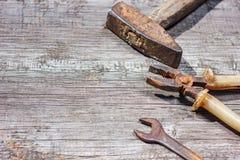 Är hjälpmedlen på träbakgrundshammareplattång och den öppna skiftnyckeln Arkivbild