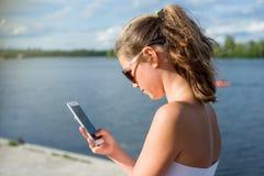 Är läs- sms för den unga gulliga tonåriga flickan på hennes smartphone, sikt från Royaltyfri Fotografi