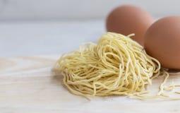 Är nya ägg för nudel på tabellen, vit bakgrund Royaltyfria Bilder