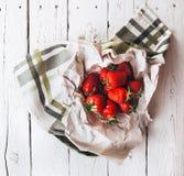 Är nya jordgubbar för handfull på den vita trätabellen Fotografering för Bildbyråer