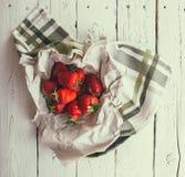 Är nya jordgubbar för handfull på den vita trätabellen Arkivbild