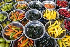 Är olika variationer för varma peppar på plattorna på räknaremarknaden Chile peppar, kajennpeppar, bitter bukett av peppar, C Royaltyfri Fotografi