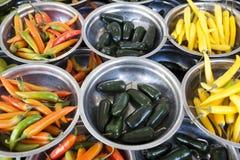 Är olika variationer för varma peppar på plattorna på räknaremarknaden Chile peppar, kajennpeppar, bitter bukett av peppar, C Royaltyfri Foto