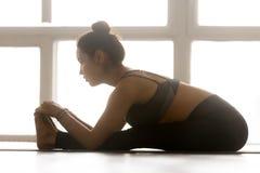 Är praktiserande yoga för den unga sportiga attraktiva kvinnan som framåtriktat placeras arkivbild