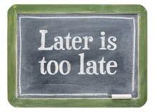 Är senare för sen - motivational text på svart tavla Arkivfoton