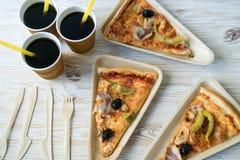 Är skivor av pizza på en träplatta Royaltyfria Bilder