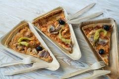 Är skivor av pizza på en träplatta Arkivfoton
