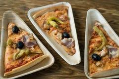 Är skivor av pizza på en träplatta Arkivbild