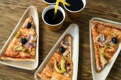 Är skivor av pizza på en träplatta Royaltyfria Foton