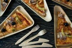 Är skivor av pizza på en träplatta Royaltyfri Foto