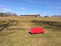 Är tillåtande avkoppling för den röda soffan i väg från ladugården Royaltyfri Bild