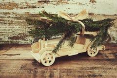 Är träbilen för barn` s lyckliga gran-träd filialer mot bakgrunden av ett gammalt tappningbräde Träbära för bil jul t Royaltyfria Bilder